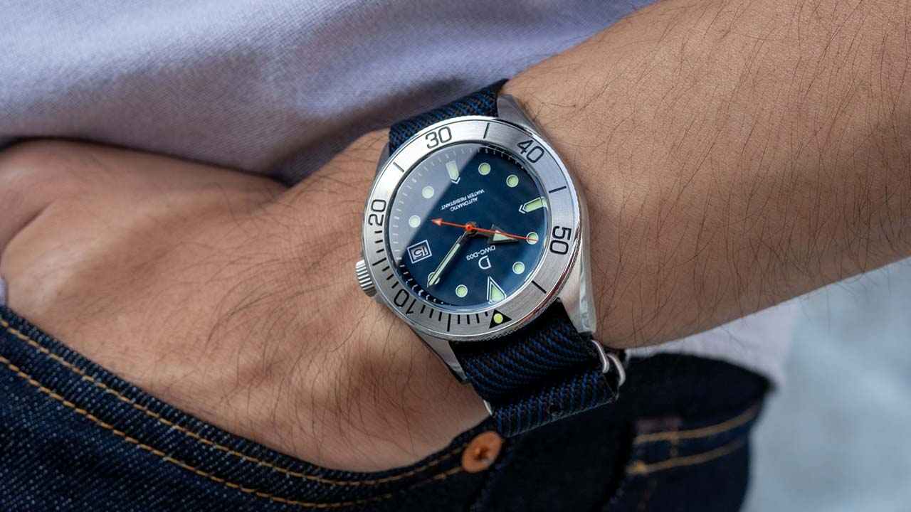 DWC dive watch with stainless steel bezel and a blue sandwich dial