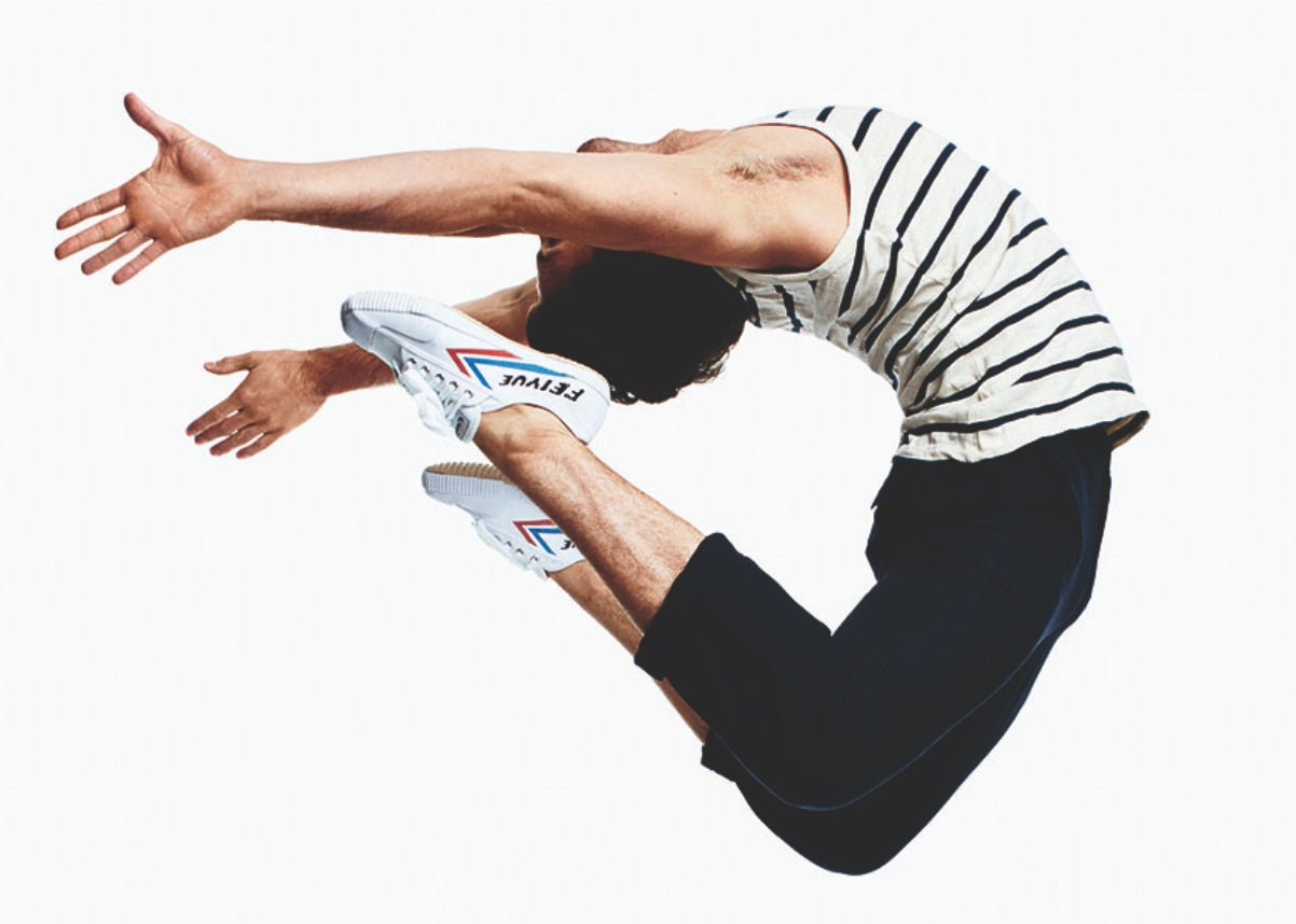 man jumping in feiyue sneaker trainers