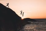Three guys cliff jumping at sunset into ocean at Llandudno Beach