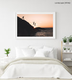 Three guys cliff jumping at sunset into ocean at Llandudno Beach in a white fine art frame
