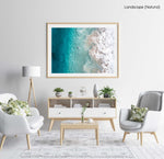Aerial surfer paddling in blue ocean away from foam in a natural fine art frame