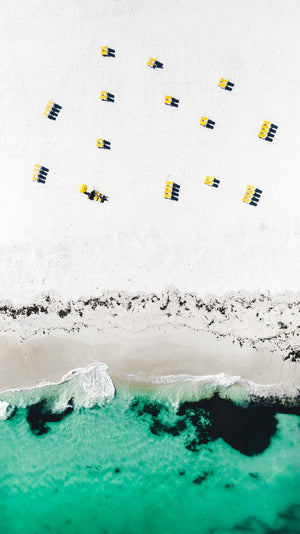 Aerial yellow beach chairs on Campsbay beach in Cape Town