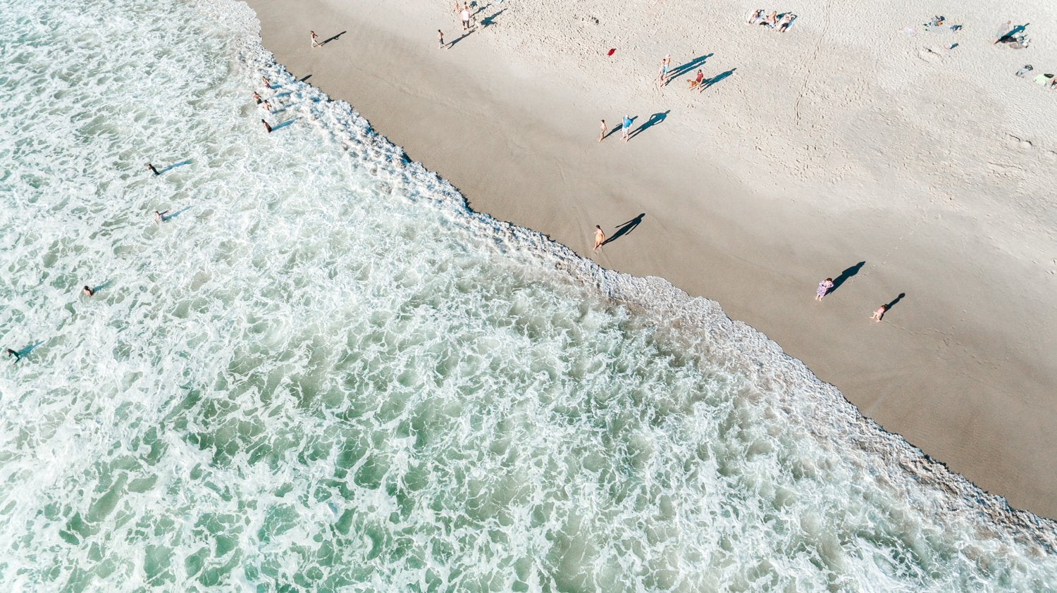 Aerial of people swimming on Llandudno beach Cape Town during sunset