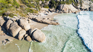 Aerial hightide waves flowing along beach boulders at Llandudno Beach in Cape Town
