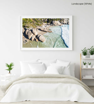 Aerial hightide waves flowing along beach boulders at Llandudno Beach in Cape Town in a white fine art frame