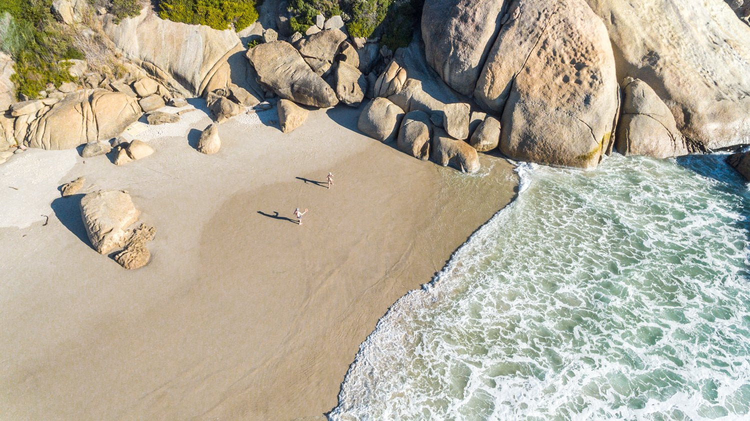 Two people playing beach bats on Llandudno Beach in Cape Town from an aerial perspective