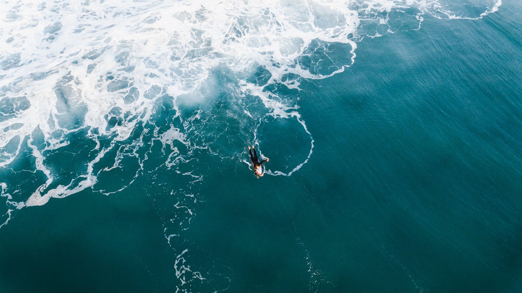 Aerial surfer paddling in dark ocean with foam
