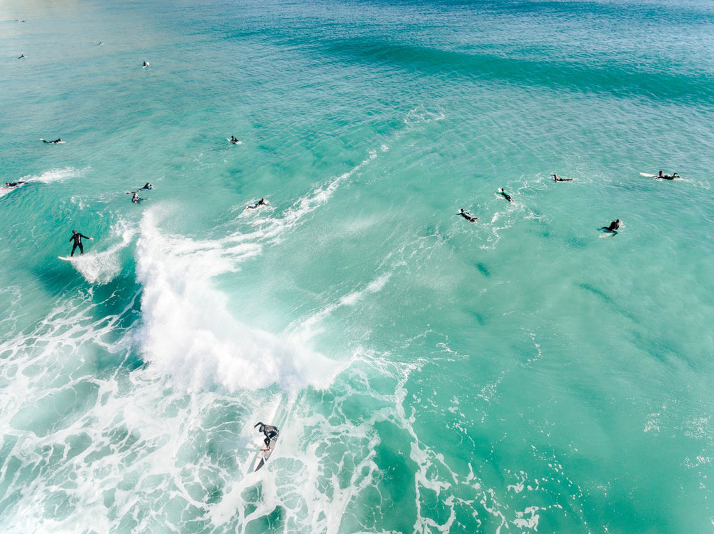 Aerial two surfers on one wave with other surfers paddling around blue swell in Cape Town