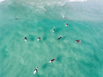 Aerial of surfers waiting and paddling for waves in sea