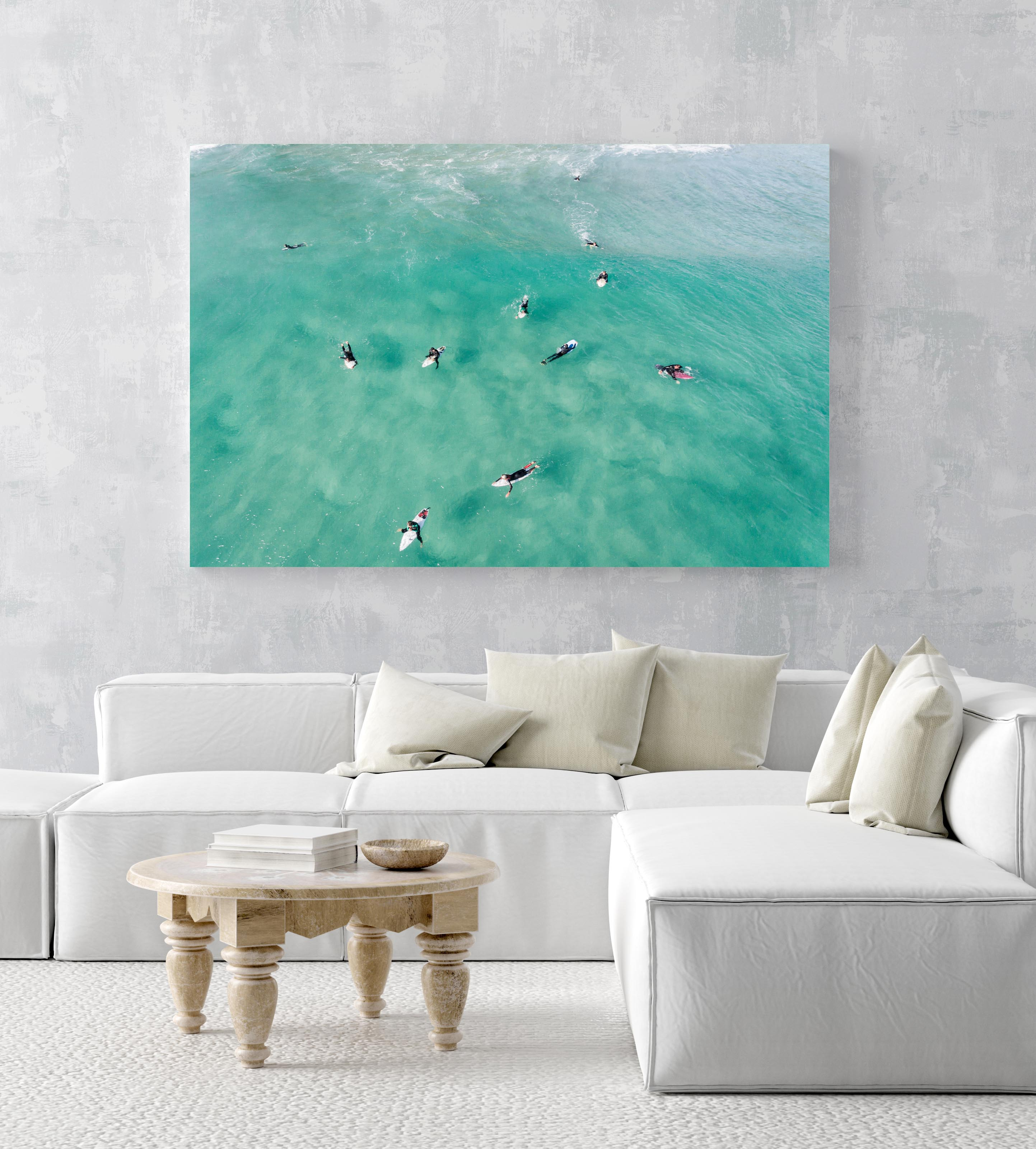 Aerial of surfers waiting and paddling for waves in sea in an acrylic/perspex frame