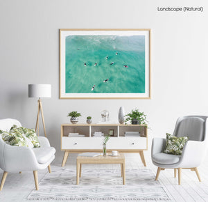 Aerial of surfers waiting and paddling for waves in sea in a natural fine art frame