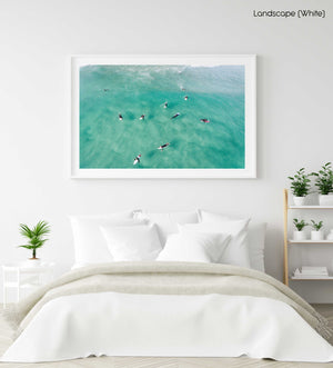 Aerial of surfers waiting and paddling for waves in sea in a white fine art frame