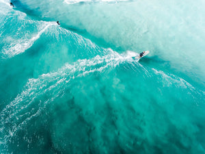 Three people surfing blue wave in Cape Town from above