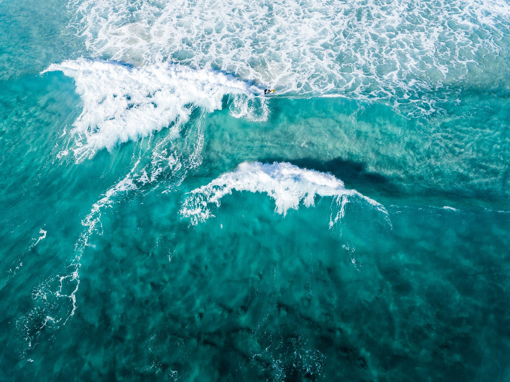 Aerial of two waves breaking in blue ocean in Cape Town