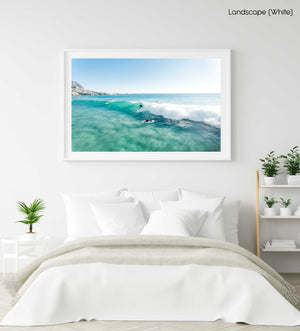 Aerial surfer going right on a small blue wave in a white fine art frame