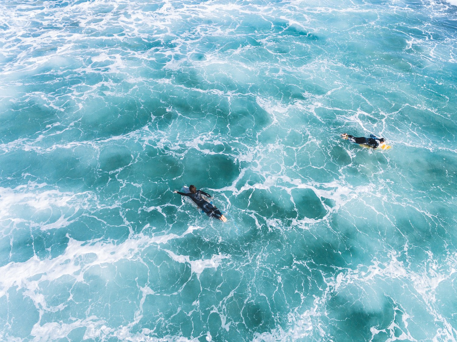 Aerial of two surfers paddling in foamy waves