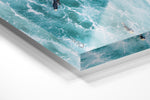 Aerial of two surfers paddling in foamy waves in an acrylic/perspex frame