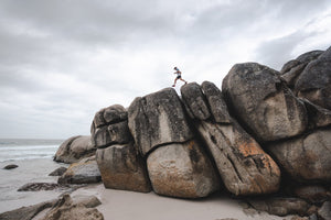 Man walking along high dark boulders on Cape Town beach