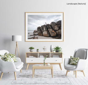 Man walking along high dark boulders on Cape Town beach in a natural fine art frame