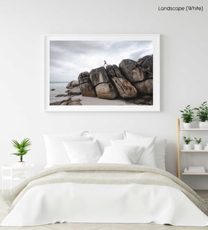Man walking along high dark boulders on Cape Town beach in a white fine art frame