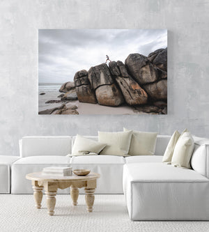 Man walking along high dark boulders on Cape Town beach in an acrylic/perspex frame