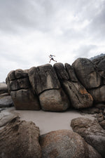Man running along beach boulders on Llandudno beach in Cape Town
