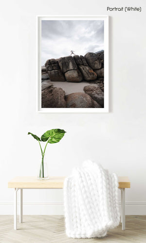 Man running along beach boulders on Llandudno beach in Cape Town in a white fine art frame