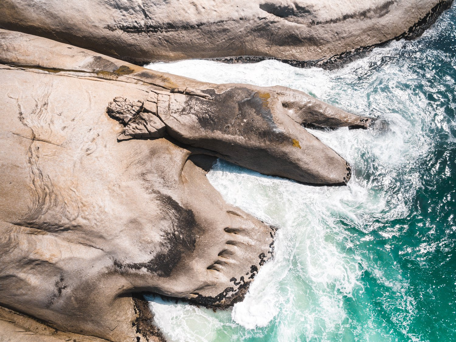 Modern shaped boulders in the ocean in Cape Town aerial