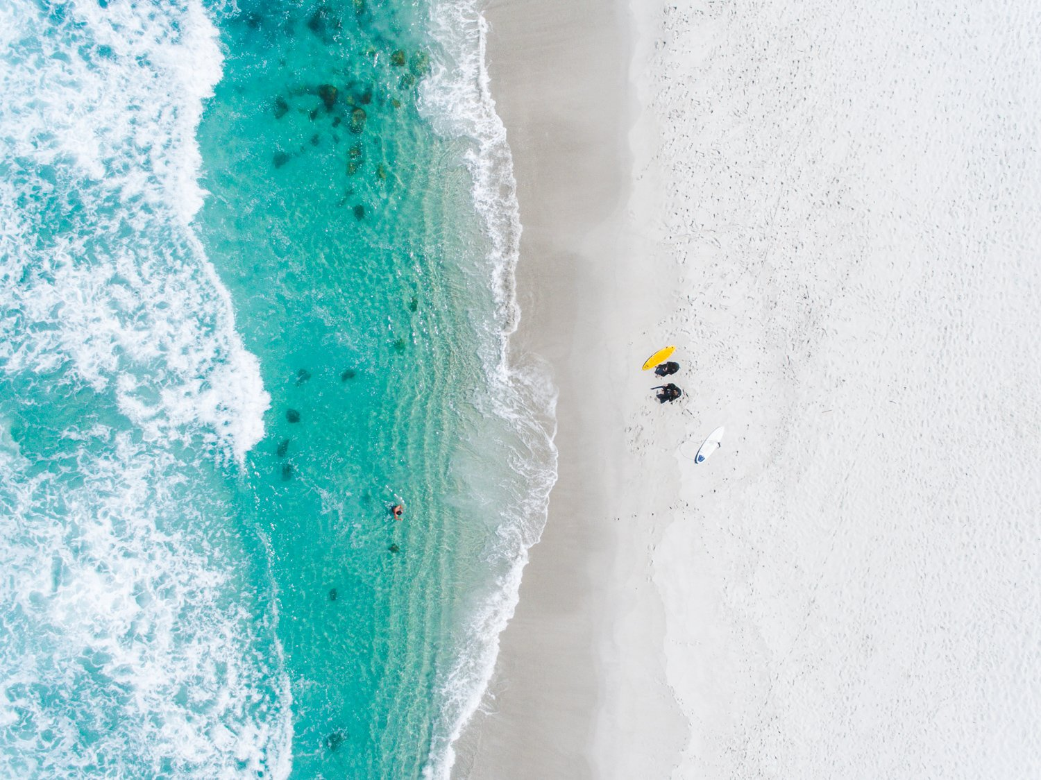 Aerial of two surfers sitting on Glen Beach in Cape Town
