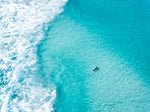 Aerial of surfer paddling in bright blue water in Cape Town