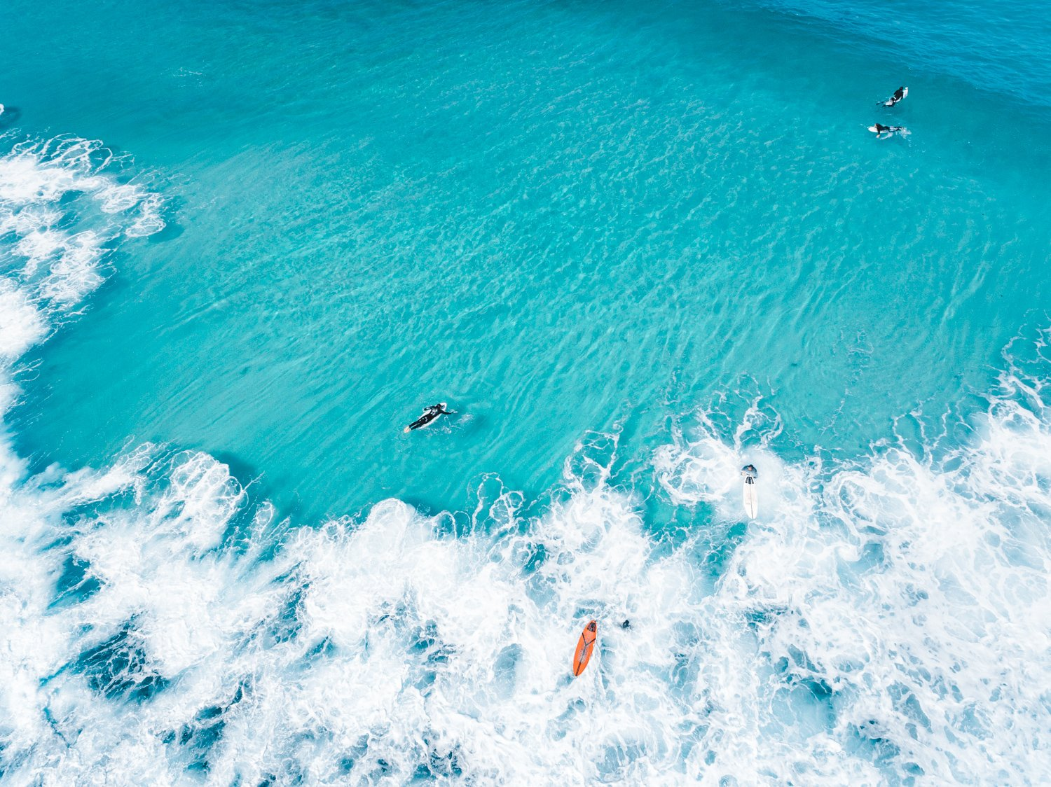 Aerial of surfers and waves in very blue waves in Cape Town