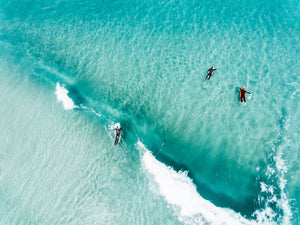 Aerial of surfers duckdiving blue wave at Glen Beach in Cape Town