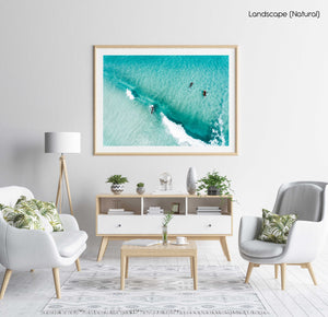 Aerial of surfers duckdiving blue wave at Glen Beach in Cape Town in a natural fine art frame