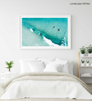 Aerial of surfers duckdiving blue wave at Glen Beach in Cape Town in a white fine art frame