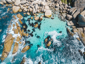 Aerial of blue water and rocks along Camps Bay in Cape Town