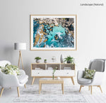 Aerial of blue water and rocks along Camps Bay in Cape Town in a natural fine art frame