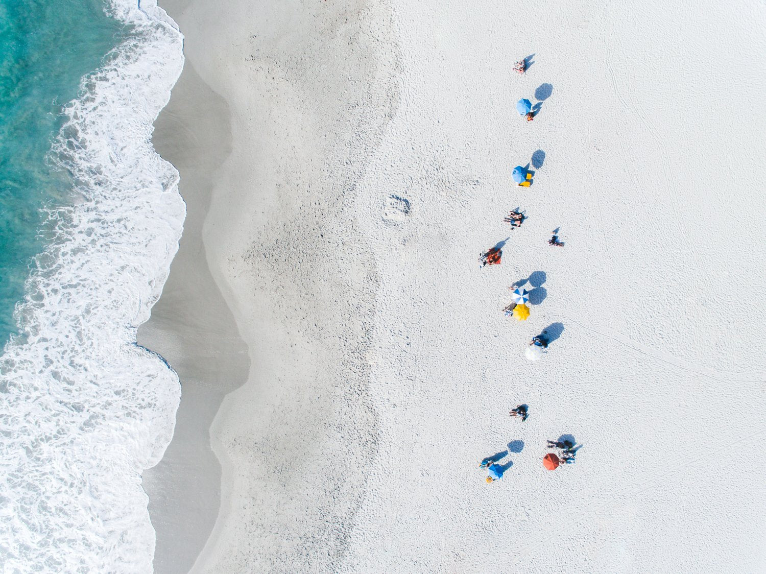 Aerial row of umbrellas on camps bay beach at waves in cape town