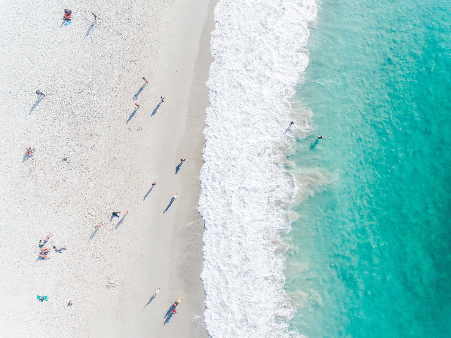 Aerial of green ocean at camps bay beach with people in cape town