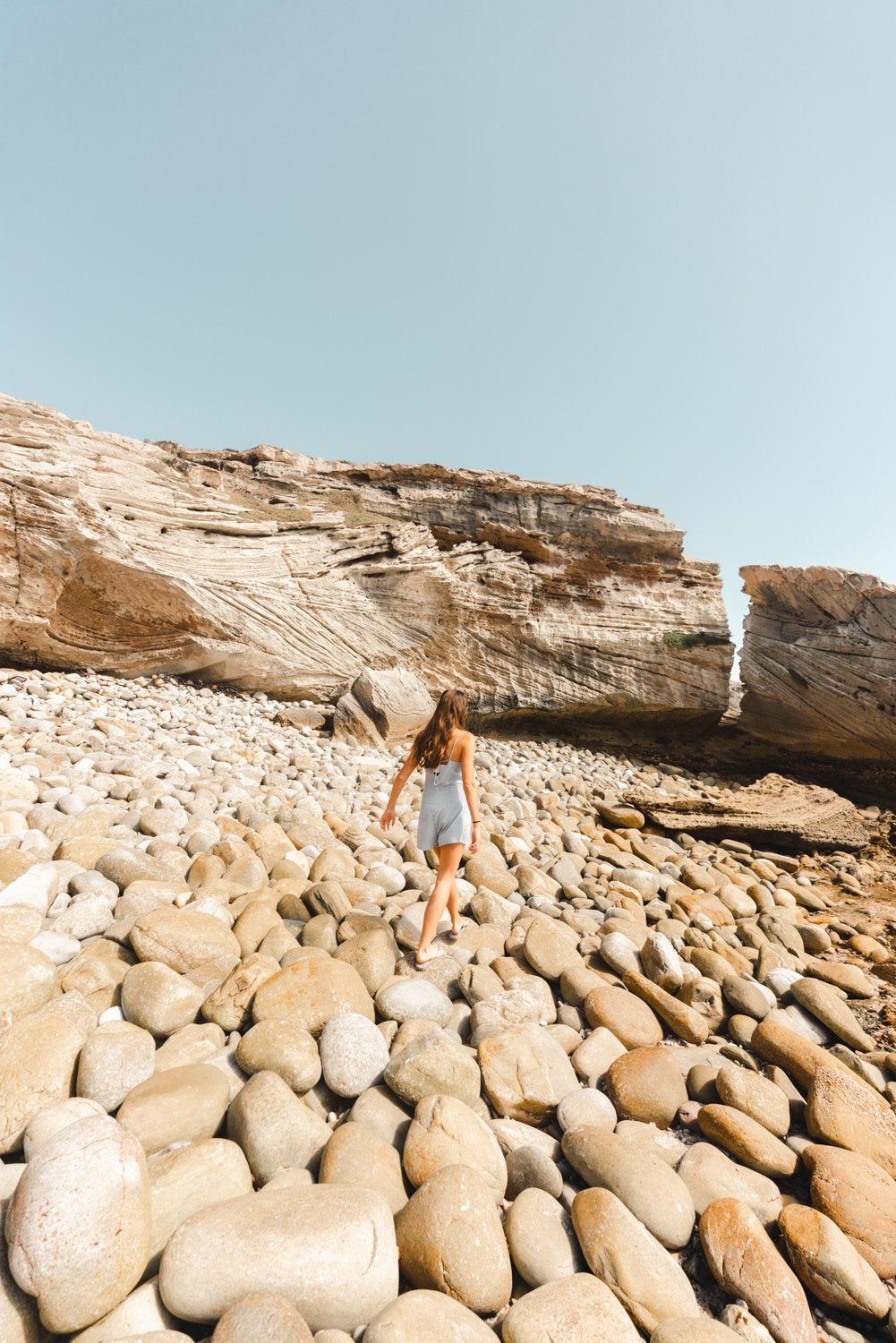 Girl walking along pebbles on beach in arniston south africa