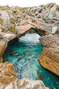 Turquoise water flowing through rock arch in arniston south africa