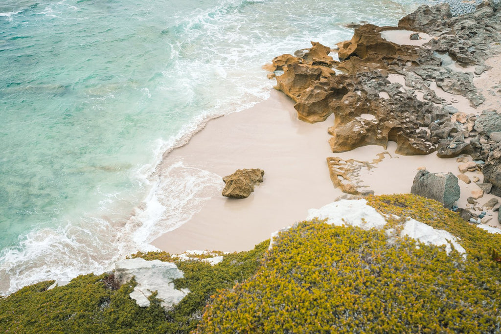 Rock in middle of a sandy beach in arniston south africa