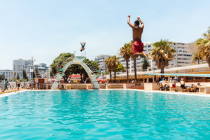 Two boys jumping in sea point pools during summer in cape town