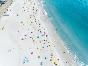 Aerial high above Camps Bay beach with lots of umbrellas and people