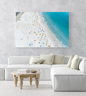 Aerial high above Camps Bay beach with lots of umbrellas and people in an acrylic/perspex frame