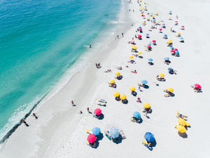 Aerial colorful umbrellas and people in sun on Camps Bay beach Cape Town