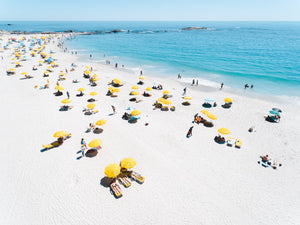 Aerial of yellow umbrellas, white sand and blue sea in Camps Bay Cape Town