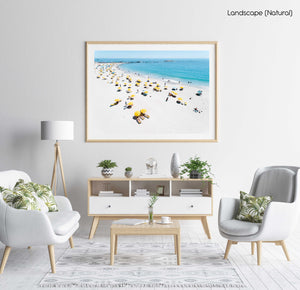 Aerial of yellow umbrellas, white sand and blue sea in Camps Bay Cape Town in a natural fine art frame