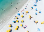 Aerial of green sea and colorful umbrellas from above on Camps Bay beach
