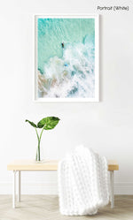 Aerial view of two surfers paddling in turquoise water and foam in a white fine art frame