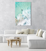 Aerial view of two surfers paddling in turquoise water and foam in a natural fine art frame